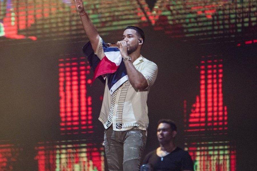 Romeo Santos con una bandera dominicana en uno de sus conciertos